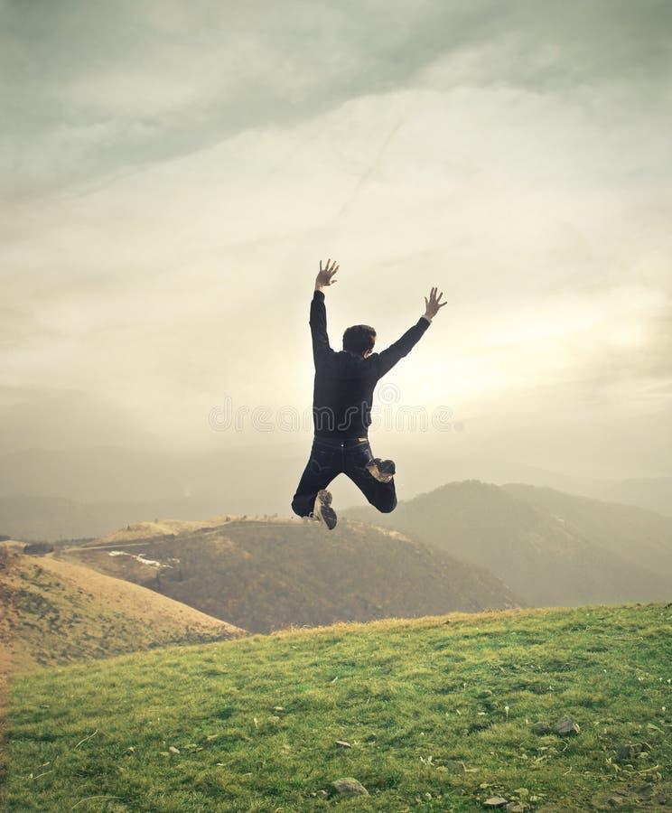 Salto joven del hombre de negocios foto de archivo