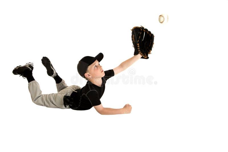 Salto joven del jugador de béisbol para hacer una captura impresionante fotografía de archivo libre de regalías