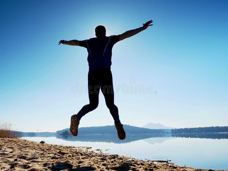 Salto loco del hombre en la playa Vuelo del deportista en la playa durante la salida del sol sobre horizonte imagen de archivo libre de regalías
