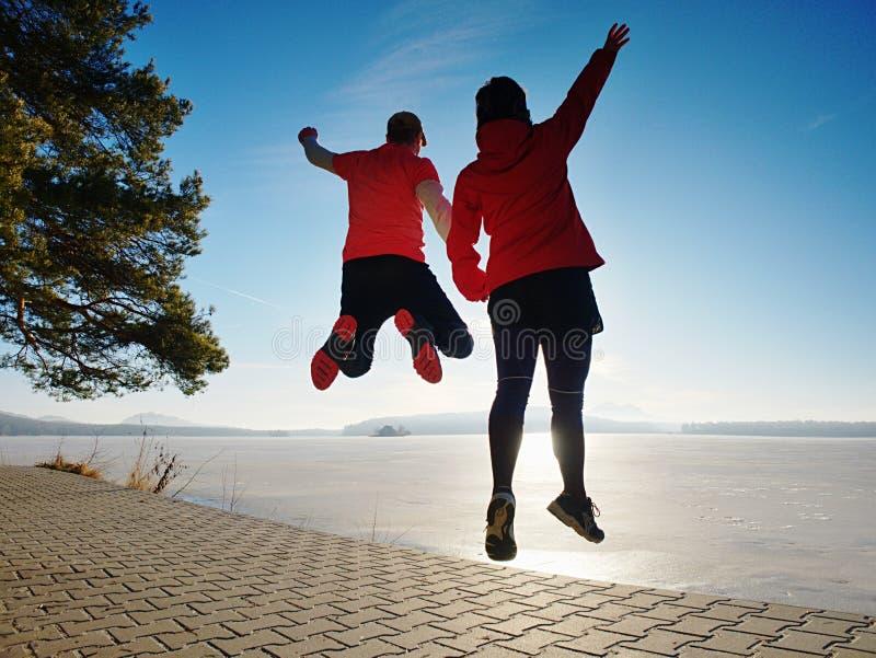 Salto louco dos pares dos esportes no trajeto do parque em torno do lago congelado fotos de stock royalty free