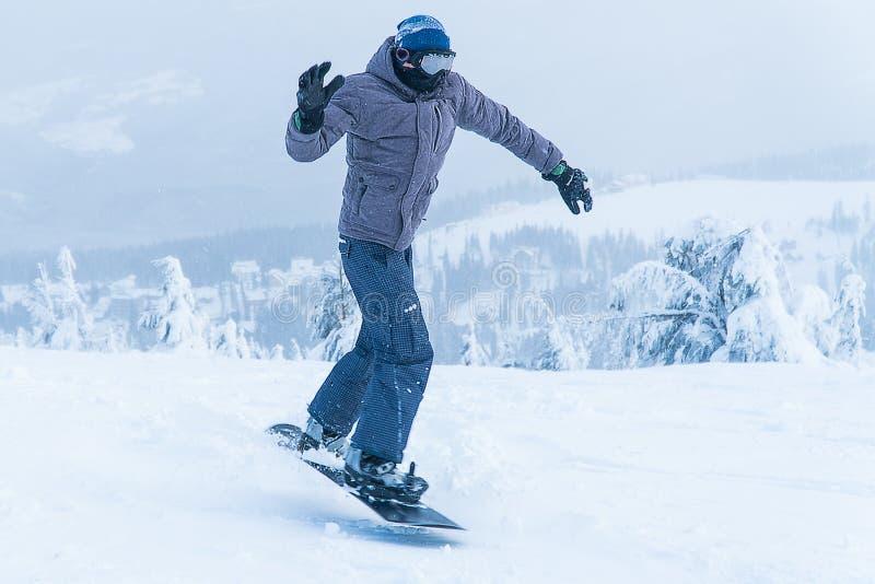 Salto masculino do snowboard da snowboarding vá nas montanhas na snowboarding do inverno da montanha da neve imagem de stock royalty free