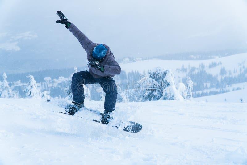 Salto masculino do snowboard da snowboarding vá nas montanhas na snowboarding do inverno da montanha da neve foto de stock royalty free