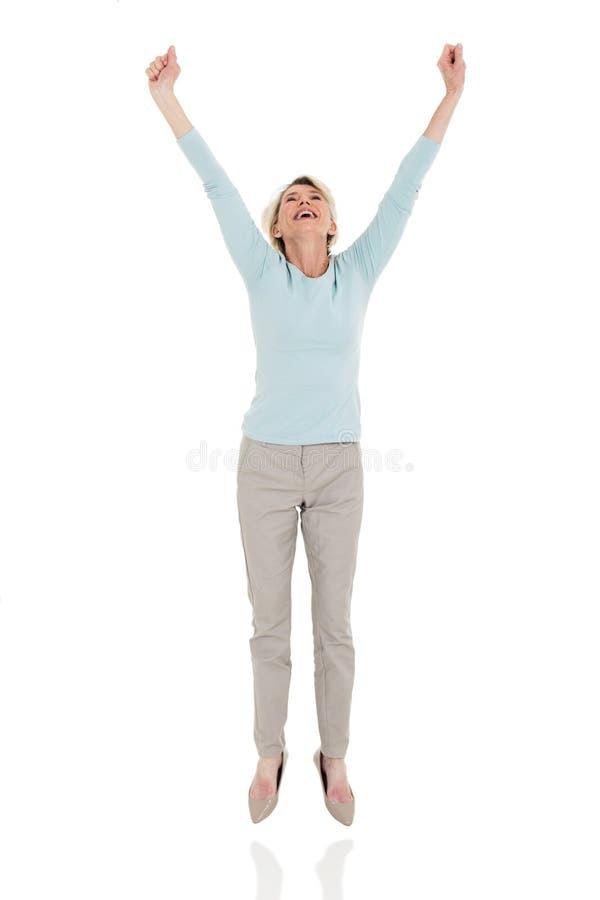 Salto mayor feliz de la mujer foto de archivo