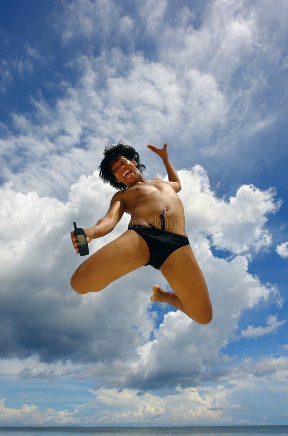 Salto molto in alto che fa pubblicità al cell-phone dal ragazzo tropicale asiatico. fotografia stock libera da diritti