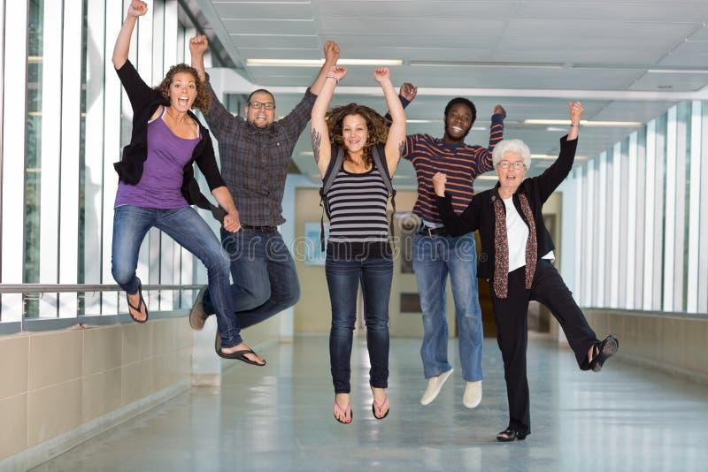 Salto multietnico emozionante degli studenti universitari fotografia stock libera da diritti