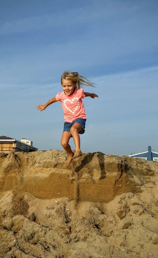 Salto rubio de la muchacha de la duna fotos de archivo libres de regalías