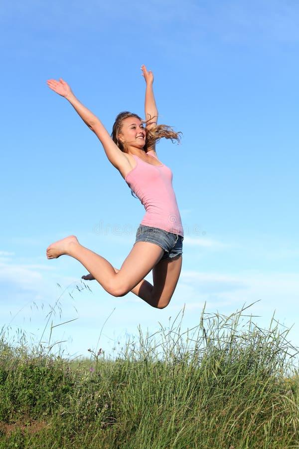 Salto rubio de la muchacha del adolescente feliz en la montaña imagen de archivo
