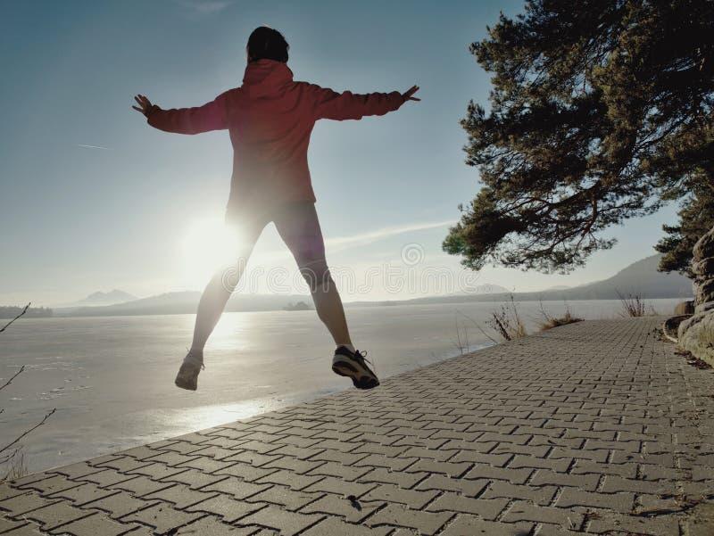 Salto y funcionamiento atléticos de la mujer de la aptitud en la playa en la puesta del sol fotos de archivo libres de regalías