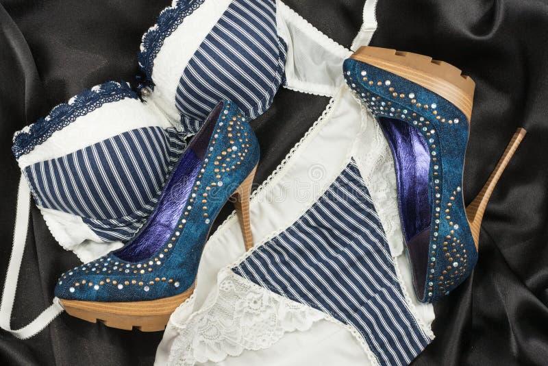 Saltos altos azuis das sapatas da roupa interior e da sarja de Nimes na seda preta Mulheres à moda modernas dos acessórios de for imagem de stock royalty free