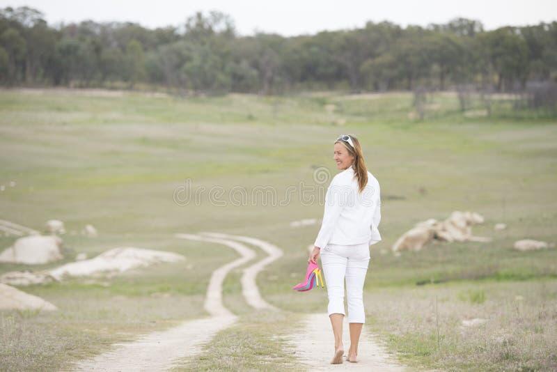 Saltos altos guardando exteriores de passeio dos pés desencapados da mulher fotografia de stock royalty free