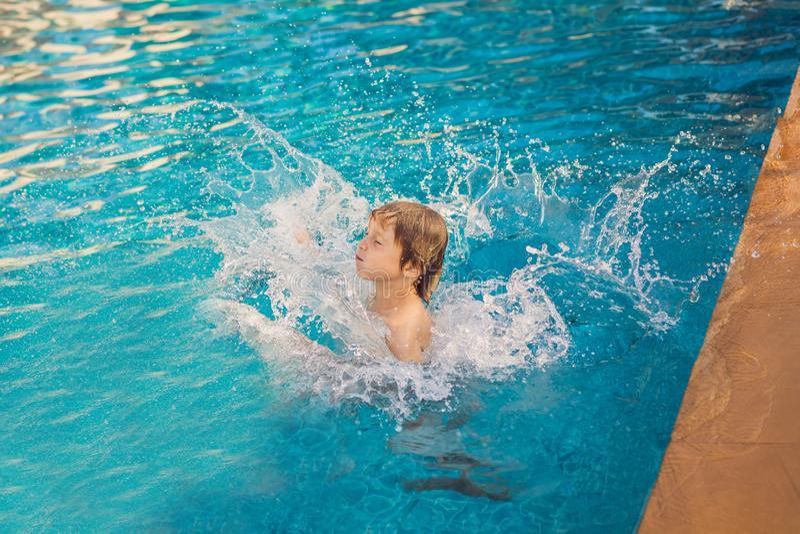Saltos del funcionamiento del niño en piscina al aire libre Childs felices para el diseño de la forma de vida fotos de archivo libres de regalías
