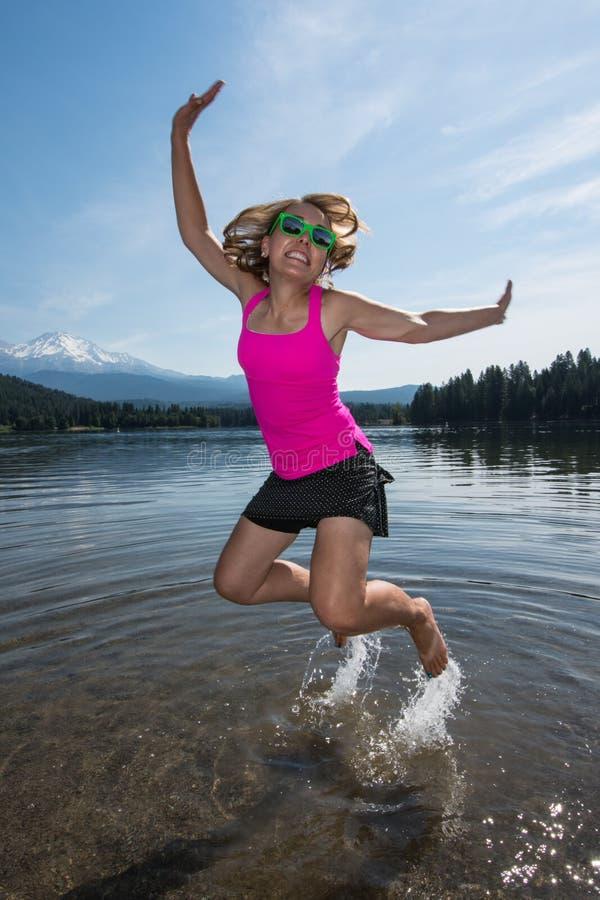 Saltos femeninos adultos en un lago, salpicando el agua detrás de sus pies en un día de verano en California, cerca del soporte S fotos de archivo