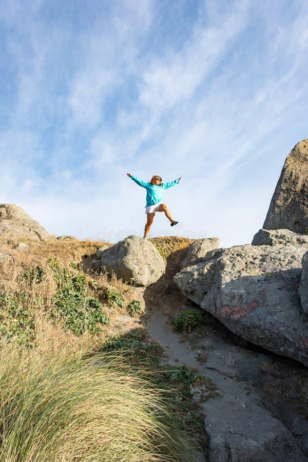 Saltos femeninos apagado de una roca grande a lo largo de la costa de Oregon imagen de archivo