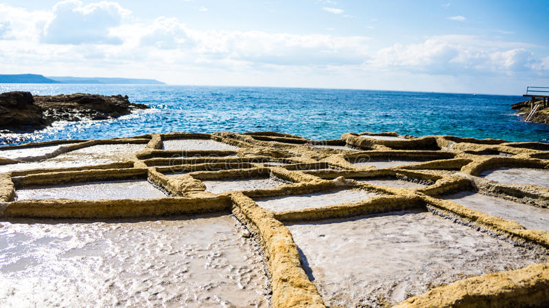 Saltpans. In Gozo, with Malta in the background royalty free stock photo