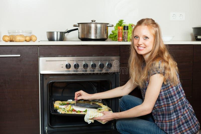 Saltwater μαγειρέματος γυναικών ψάρια στο φούρνο στην κουζίνα στοκ εικόνα