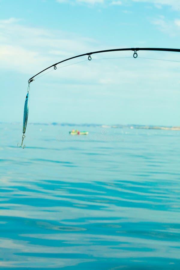Saltwater που αλιεύει - ράβδος με το wobbler και το μπλε θαλάσσιο νερό στοκ εικόνα