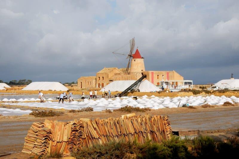 Saltworks nabijgelegen marsala met oude windmolenarbeiders, Sicilië royalty-vrije stock afbeeldingen