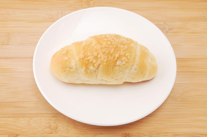 Salty butter roll bread on plate on table. Salty butter roll bread on plate isolated on table stock image