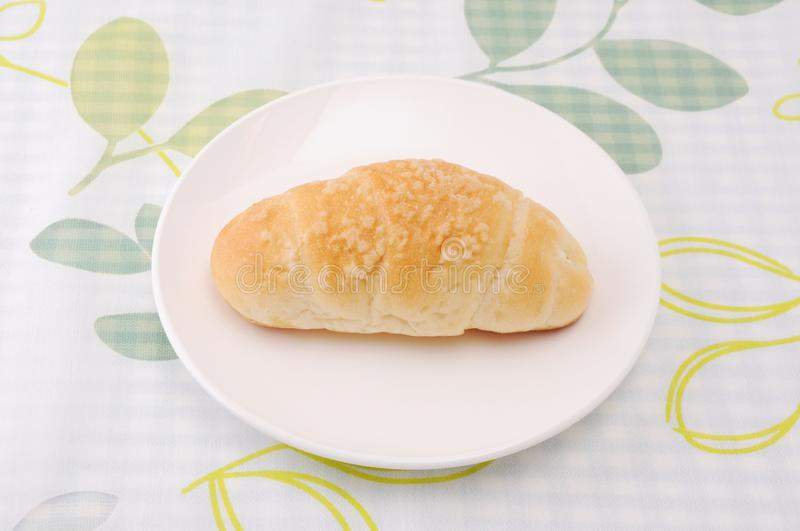 Salty butter roll bread on plate on table. Salty butter roll bread on plate isolated on table royalty free stock images