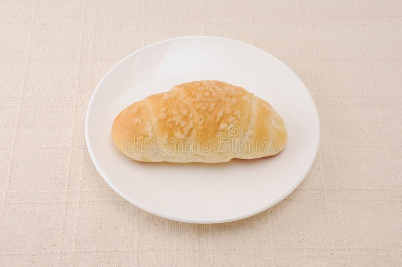 Salty butter roll bread on plate on table. Salty butter roll bread on plate isolated on table royalty free stock photography
