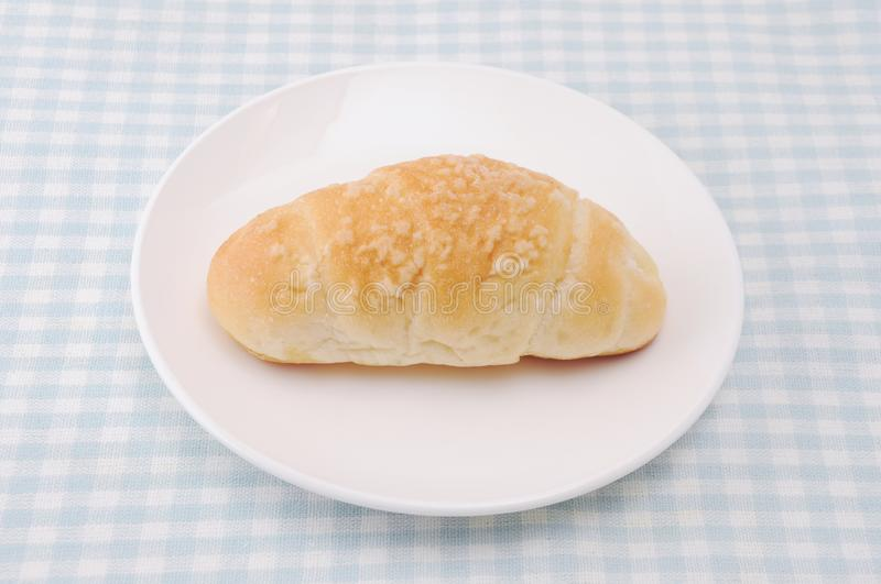 Salty butter roll bread on plate on table. Salty butter roll bread on plate isolated on table stock photo