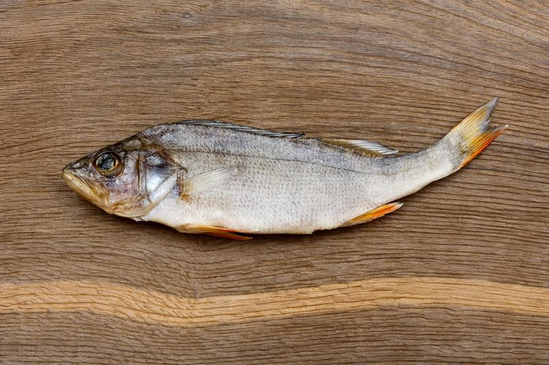 Salty dry river fish perch, bass on a wooden impressive background. stock photography