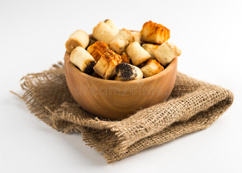 Salty party snack in wooden bowl on natural jute. White background. stock photos