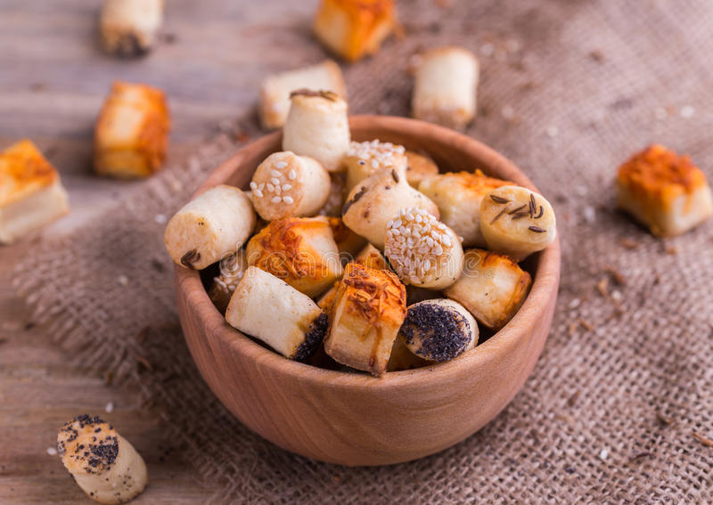 Salty party snacks in wooden bowl on natural background. royalty free stock images