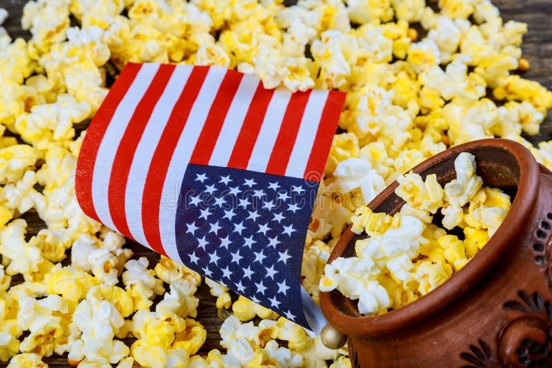 Salty popcorn in a wooden cup American flag flying, flag USA is on a white table. Popcorn lies around the bowl. stock photos