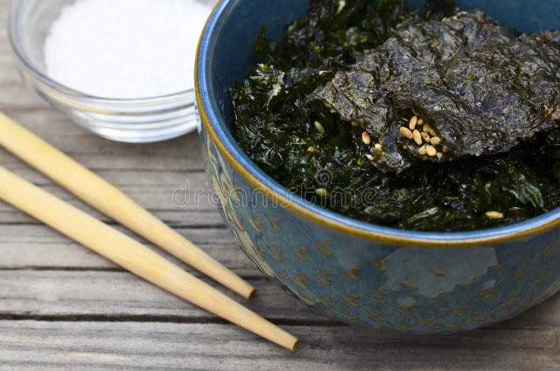 Salty roasted dried seaweed nori with sesame seeds in a blue bowl on old wooden table.Healthy snack,Korean food concept. Selective focus royalty free stock image
