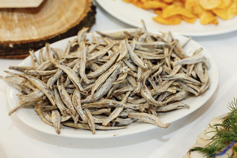 salty smoked anchovies on wooden desk on table, wedding reception. beer bar and snacks. catering in restaurant stock image