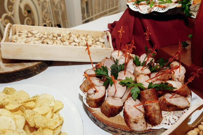 Salty smoked sausage and chips nuts on wooden desk on table, wed stock photography