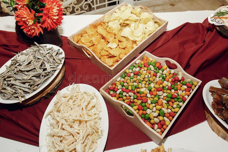 Salty smoked squid and anchovies, chips and nuts on wooden desk royalty free stock images