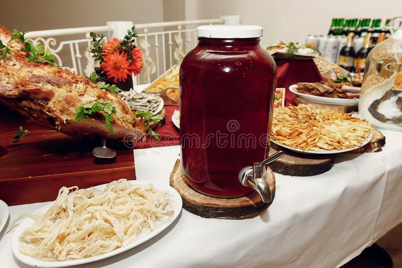 Salty smoked squid and anchovies and ham and drink on wooden desk on table, wedding reception. beer bar and snacks. catering in r. Estaurant royalty free stock photos