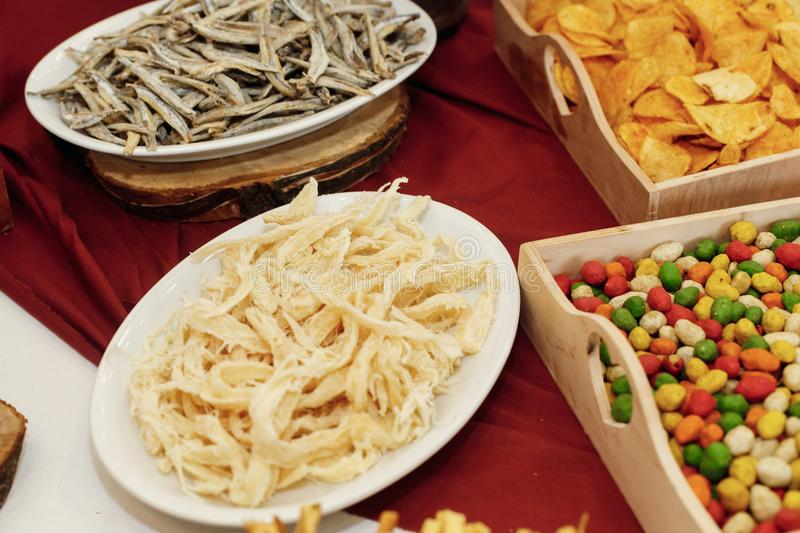 salty smoked squid and anchovies on wooden desk on table, wedding reception. beer bar and snacks. catering in restaurant stock image