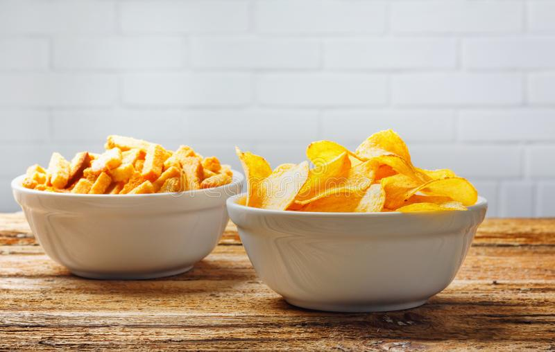 Chips, crackers in bowls on wooden table on brick wall royalty free stock images