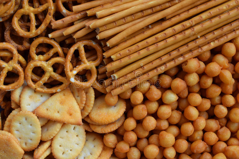 Salty snacks. Crackers, pretzel, salted straws, nuts. Junk food for beer or cola. Photographed with natural light.  stock images