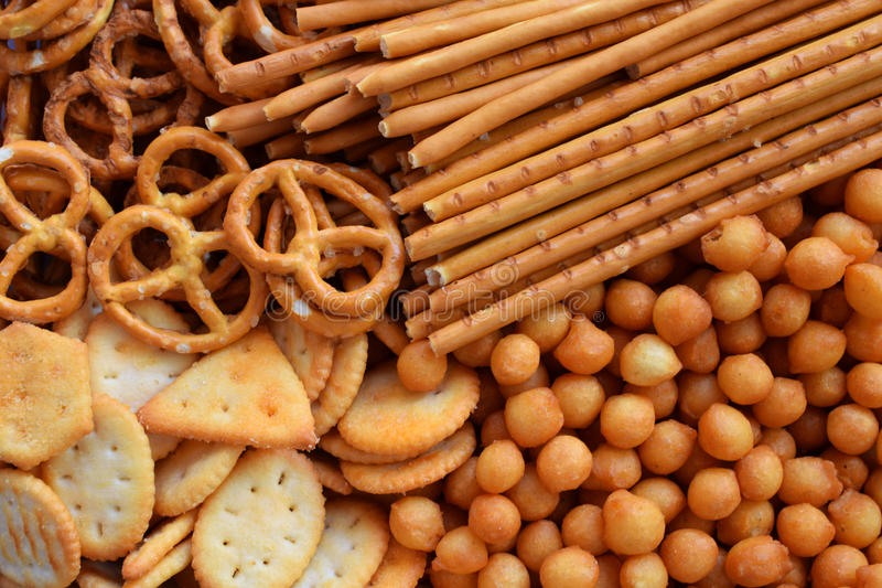 Salty snacks. Crackers, pretzel, salted straws, nuts. Junk food for beer or cola. Photographed with natural light. Salty snacks. Crackers, pretzel, salted stock image