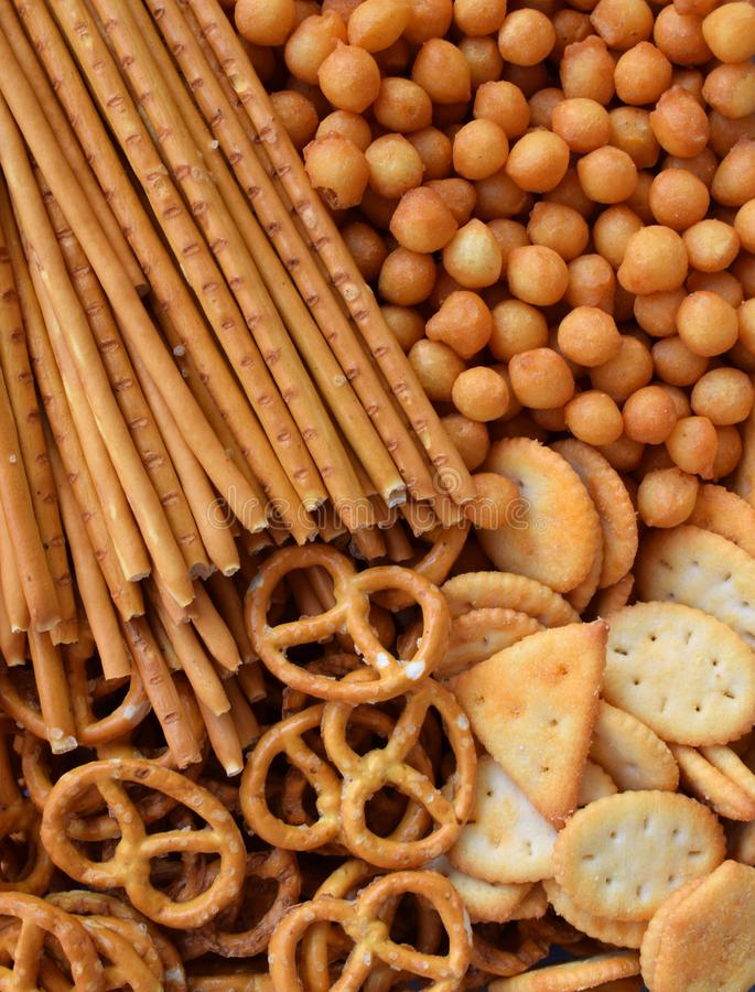 Salty snacks. Crackers, pretzel, salted straws, nuts. Junk food for beer or cola. Photographed with natural light.  stock photos