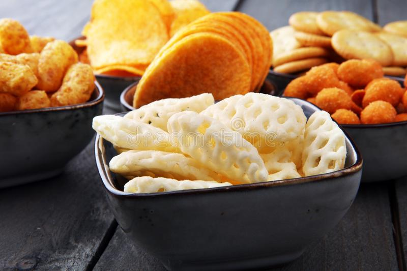 Salty snacks. Pretzels, chips, crackers in bowls. royalty free stock images