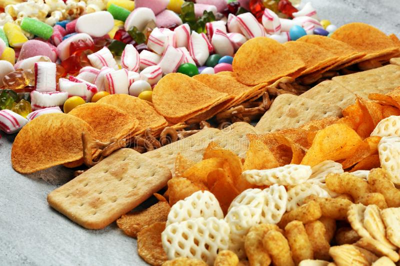 Salty snacks. Pretzels, chips, crackers and candy sweets on table stock photo