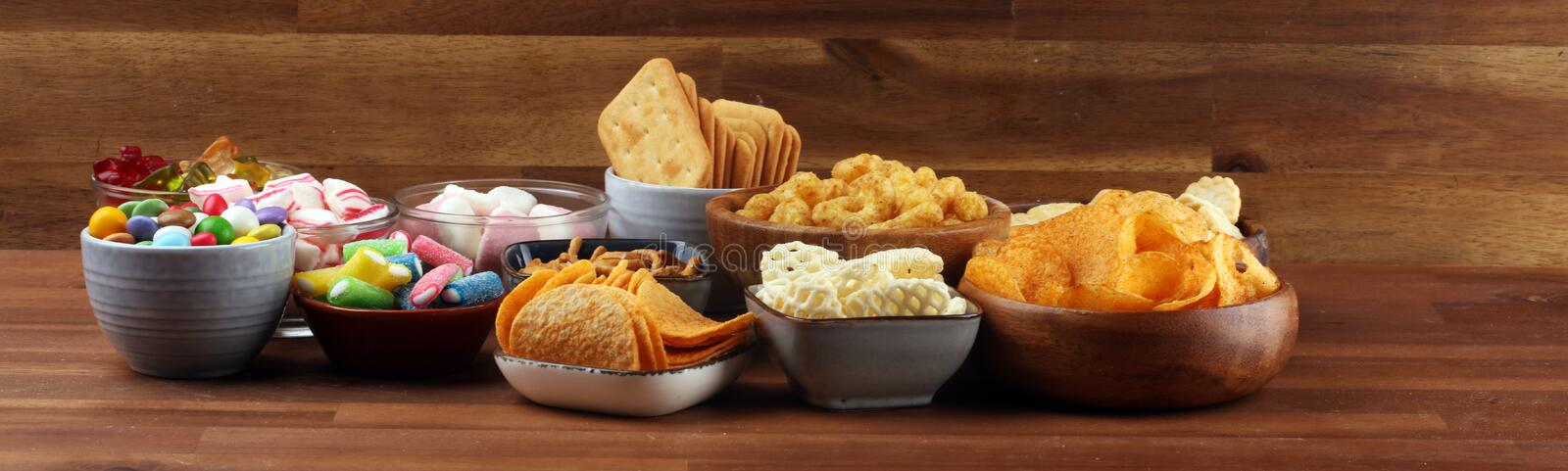 Salty snacks. Pretzels, chips, crackers and candy sweets on table stock photos