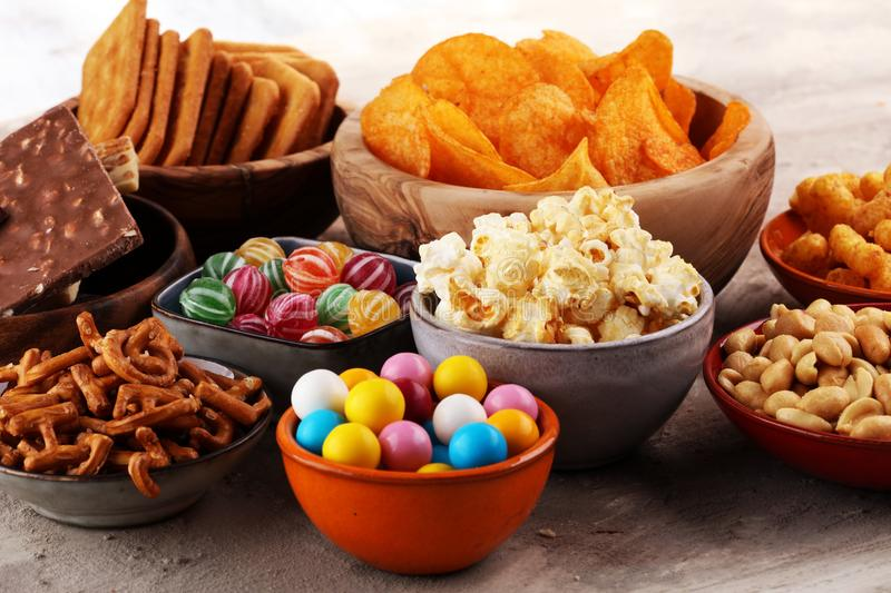 Salty snacks. Pretzels, chips, crackers in wooden bowls. royalty free stock images