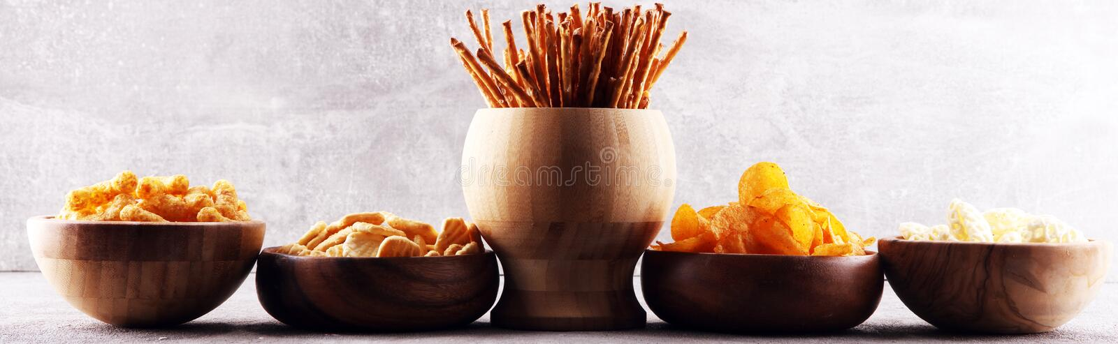 Salty snacks. Pretzels, chips, crackers in wooden bowls stock image