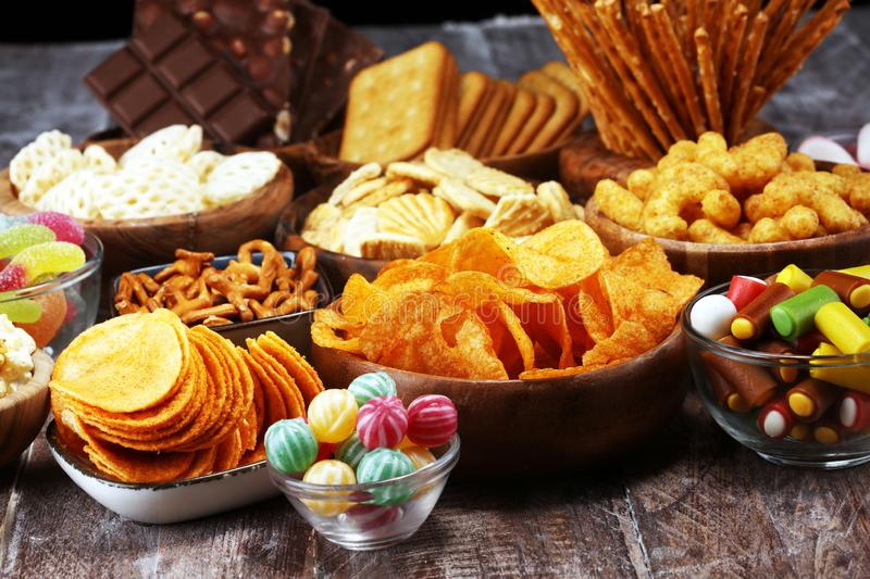 Salty snacks. Pretzels, chips, crackers in wooden bowls on table stock image
