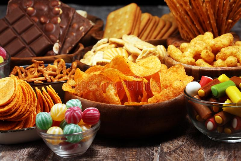 Salty snacks. Pretzels, chips, crackers in wooden bowls on table royalty free stock photo