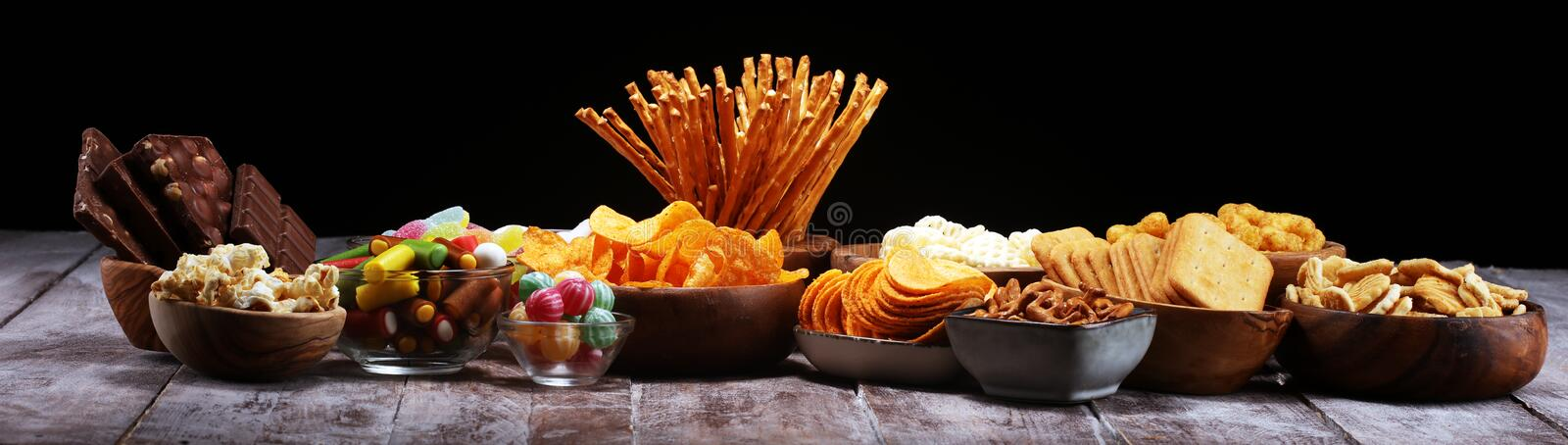 Salty snacks. Pretzels, chips, crackers in wooden bowls on table stock images
