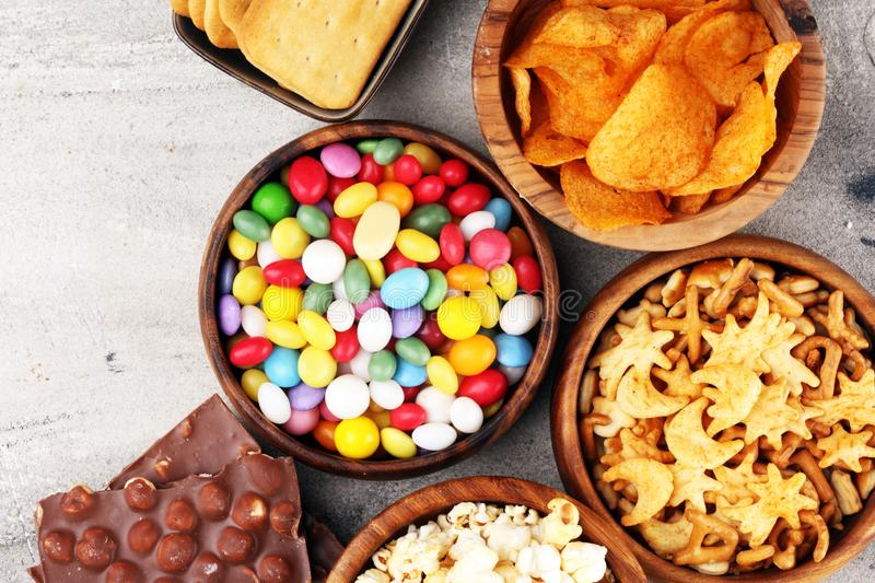 Salty snacks. Pretzels, chips, crackers in wooden bowls and candy and chocolate on table stock images