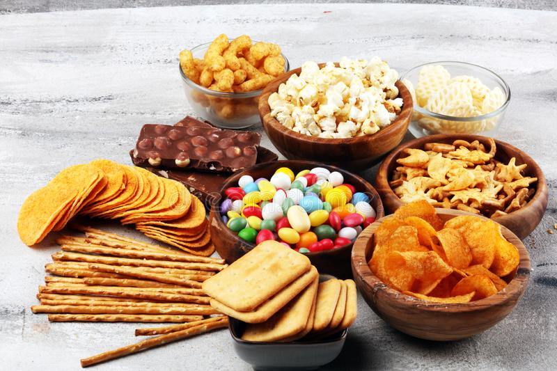 Salty snacks. Pretzels, chips, crackers in wooden bowls and candy and chocolate on table royalty free stock photography