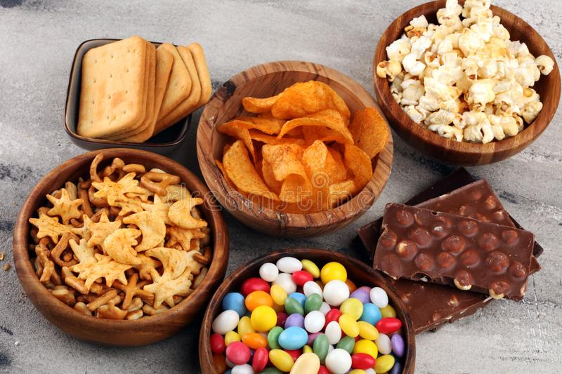 Salty snacks. Pretzels, chips, crackers in wooden bowls and candy and chocolate on table stock photography
